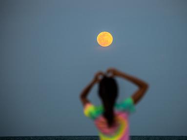 Bulan Purnama Super Pink terlihat di latar belakang saat orang-orang bersantai di pantai di Miami Beach, Florida, Senin (26/4/2021). Super Pink Moon merupakan fenomena alam ketika posisi bulan purnama berada terdekat dengan bumi. (CHANDAN KHANNA / AFP)