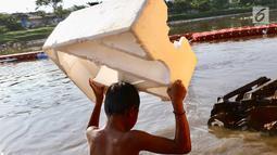 Seorang anak membawa styrofoam untuk berenang di Kanal Banjir Barat, Jakarta, Jumat (23/3). Anak-anak nekat berenang di lokasi ini meski berbahaya bagi kesehatan dan keselamatan. (Liputan6.com/Immanuel Antonius)