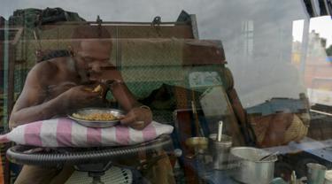 Seorang sopir makan di sebuah truk yang diparkir di terminal di Chennai (19/9/2019). Layanan transportasi darat menyerukan pemogokan satu hari untuk memprotes kenaikan pinalti di bawah Undang-undang Kendaraan Bermotor (Amandemen) yang baru. (AFP Photo/Arun Sankar)