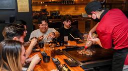 Pengunjung menikmati hidangan teppanyaki Jepang di Chinatown, Melbourne, Australia, Jumat (22/10/2021). Lima juta warga Melbourne kini akhirnya bisa keluar rumah lagi. (William WEST/AFP)