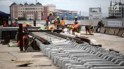 Pemandangan saat pekerja memasang rel di Depo LRT, Kelapa Gading, Jakarta Utara, Kamis (25/1). Pengiriman kereta pertama ke Indonesia dijadwalkan April 2018. (Liputan6.com/Arya Manggala)