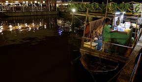 Pedagang menunggu pembeli saat menjajakan dagangannya di atas perahu di Alun-Alun Sungai Kapuas, Pontianak, Kalimantan Barat, Kamis (12/4). Akibat dilarang, para pedagang ini memilih berdagang di atas perahu. (Liputan6.com/Johan Tallo)