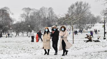 Orang-orang yang mengenakan masker berjalan di atas salju di Primrose Hill di London saat ibu kota mengalami hujan salju yang jarang terjadi pada Minggu (24/1/2021). Hujan salju langka itu membawa kegembiraan di tengah penguncian atau penutupan wilayah (lockdown) secara nasional. (JUSTIN TALLIS/AFP)