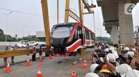 Proses perdana gerbong kereta layang ringan atau light rail transit (LRT) ke lintasan rel di Stasiun Harjamukti, Cibubur, Minggu (13/10/2019). Sebanyak satu rangkaian (trainset) yang terdiri dari 6 kereta (car) diangkat ke atas rel menggunakan Gantry Crane. (merdeka.com/Iqbal S Nugroho)