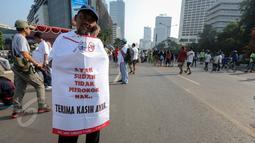 """Aktivis mengenakan atribut bertuliskan """"Ayah Sudah Tidak Merokok Nak"""" saat peringatan Hari Tanpa Tembakau di Bundaran HI, Jakarta, Minggu (31/5). Gerakan ini menyerukan para perokok agar tidak merokok selama 24 jam serentak. (Liputan6.com/Faizal Fanani)"""