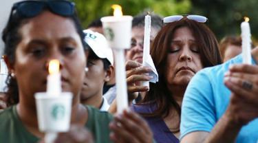 Seorang wanita berdoa sambil memegang lilin  saat menghadiri acara untuk korban penembakan brutal di festival kuliner Gilroy Garlic di Gilroy, California (29/7/2019). Tiga orang tewas dan sedikitnya puluhan orang terluka akibat kejadian tersebut. (AFP Photo/Mario Tama)