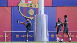 Penyerang Barcelona, Ansu Fati (kiri) melakukan pemanasan saat mengikuti sesi latihan tim di Joan Gamper Sports City, Spanyol (16/9/2019). Barcelona akan menghadapi wakil Jerman, Borussia Dortmund pada grup F Liga Champions di Signal Iduna Park. (AFP Photo/Pau Barrena)
