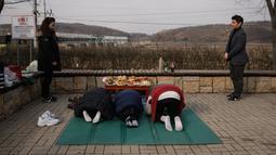 "Kim Jung-ae dari Korea Utara (kiri) menyaksikan keluarganya memberikan penghormatan kepada kerabat dan leluhur selama Tahun Baru Imlek di ""desa harapan"" Imjingak, dekat zona demiliterisasi yang memisahkan kedua Korea di Paju, Selasa (5/2). (Ed JONES/AFP)"