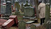 Warga melihat batu nisan Yahudi yang rusak usai serangan vandalisme di Chesed Shel Emeth Cemetery di University City, St Louis, Missouri, (21/2). Setidaknya lebih dari 100 batu nisan rusak di pekuburan itu. (Robert Cohen /St. Louis Post-Dispatch via AP)