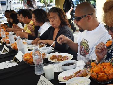 Peserta berlomba menyelesaikan makan cabai Habanero dalam Habanero Eating Contest di Restoran Chichen Itza, Los Angeles, Minggu (21/6). Dalam lomba ini setiap peserta diberikan 60 cabai Habanero dengan waktu 20 menit. (AFP PHOTO/Mark RALSTON)