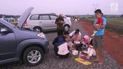 Pemudik menyantap hidangan berbuka puasa di pinggir Tol Fungsional Pemalang-Batang, Jawa Tengah, Minggu (10/6). Mereka memanfaatkan waktu istirahat di pinggir tol yang belum rampung dibangun. (Liputan6.com/Arya Manggala)
