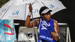Petenis Amerika Serikat, Sloane Stephens, memegang payungnya sendiri saat diguyur hujan pada laga Italian Open 2020 di Foro Italico, Selasa (15/9/2020). (AFP/Clive Brunskill/pool)