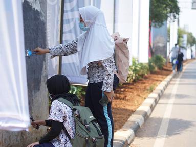 Pelajar mengecat  coretan yang mengotori tembok  saat kericuhan dalam unjuk rasa di Senayan, Jakarta, Jumat (4/10/2019). Para siswa dan alumni SMA menutup coret-coretan  itu sekaligus mengampanyekan cinta damai dalam praktik demokrasi di Indonesia. (Liputan6.com/Immanuel Antonius)