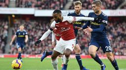 Striker Arsenal, Alexandre Lacazette, berusaha melewati bek Fulham, Maxime Le Marchand, pada laga Premier League di Stadion Emirates, London, Selasa (1/1). Arsenal menang 5-1 atas Fulham. (AFP/Glyn Kirk)