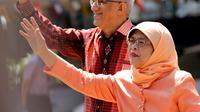 Halimah Yacob melambaikan tangan ke pendukungnya saat tiba untuk menyerahkan berkas pencalonan presiden di Singapura, Rabu (13/9). Halimah telah malang melintang di perpolitikan Singapura, serta menjadi ketua parlemen sejak 2013. (AP Photo/Wong Maye-E)