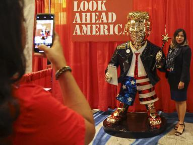 Seorang perempuan berfoto dengan patung emas Donald Trump pada Konferensi Politik Konservatif (CPAC) di Orlando, Florida, Jumat (26/2/2021). Kemunculan patung emas yang lebih besar dari ukuran pria dewasa di acara tersebut menjadi viral. (Sam Thomas/Orlando Sentinel via AP)