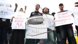 Massa yang tergabung dalam Aliansi Jurnalis Gorontalo membawa sejumlah poster saat menggelar aksi menolak RUU KUHP di Gorontalo, Senin (23/9/2019). Dalam aksinya massa bergerak dari Bundaran Saronde Gorontalo menuju Gerbang Kampus Universitas Negeri Gorontalo (UNG). (Liputan6.com/Arfandi Ibrahim)