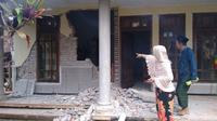 Dua warga mengamati rumah yang mengalami kerusakan akibat dampak dari Gempabumi Selatan Malang M 6,1 di Kabupaten Malang, Sabtu (10/4). (Dok BPBD Kabupaten Malang)