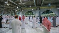 "Warga Saudi dan ekspatriat melakukan sholat ""Al Fajr"" di Masjidil Haram di kota suci Mekkah (18/10/2020). Saudi sebelumnya menutup Masjidil Haram untuk umum selama berbulan-bulan sebagai upaya menghentikan penyebaran virus corona. (AFP/STR)"