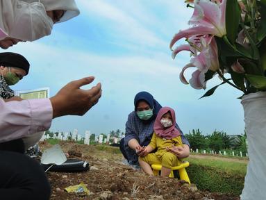 Warga berdoa di depan pusara keluarganya saat ziarah kubur di TPU Srengseng Sawah 2, Jagakarsa, Jakarta Selatan, Senin (17/5/2021). Hari ini seluruh TPU di wilayah DKI dibuka untuk umum dengan menerapkan protokol kesehatan seperti pembatasan pengunjung dan waktu berziarah. (merdeka.com/Arie Basuki)