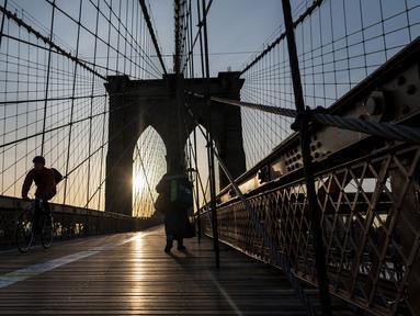 Pengendara sepeda menyeberangi Jembatan Brooklyn melintasi East River ke Manhattan di New York City, 7 Januari 2019. Brooklyn Bridge yang memiliki panjang 1.825 meter itu merupakan salah satu jembatan suspensi tertua di AS. (Johannes EISELE/AFP)