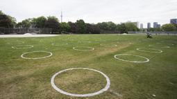 Sejumlah lingkaran putih terlihat di Taman Trinity Bellwoods, Toronto, Kanada, Kamis (28/5/2020). Taman Trinity Bellwoods digambari lingkaran-lingkaran putih sebagai proyek uji coba untuk mendorong warga melakukan jaga jarak fisik (physical distancing) selama pandemi COVID-19. (Xinhua/Zou Zheng)