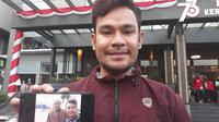Seorang suporter, Rachmat Hidayat, menunjukkan fotonya bersama pemain Timnas Indonesia U-23, Hansamu Yamaha, Senin (20/8/2018). (Bola.net/Fitri Apriyani)