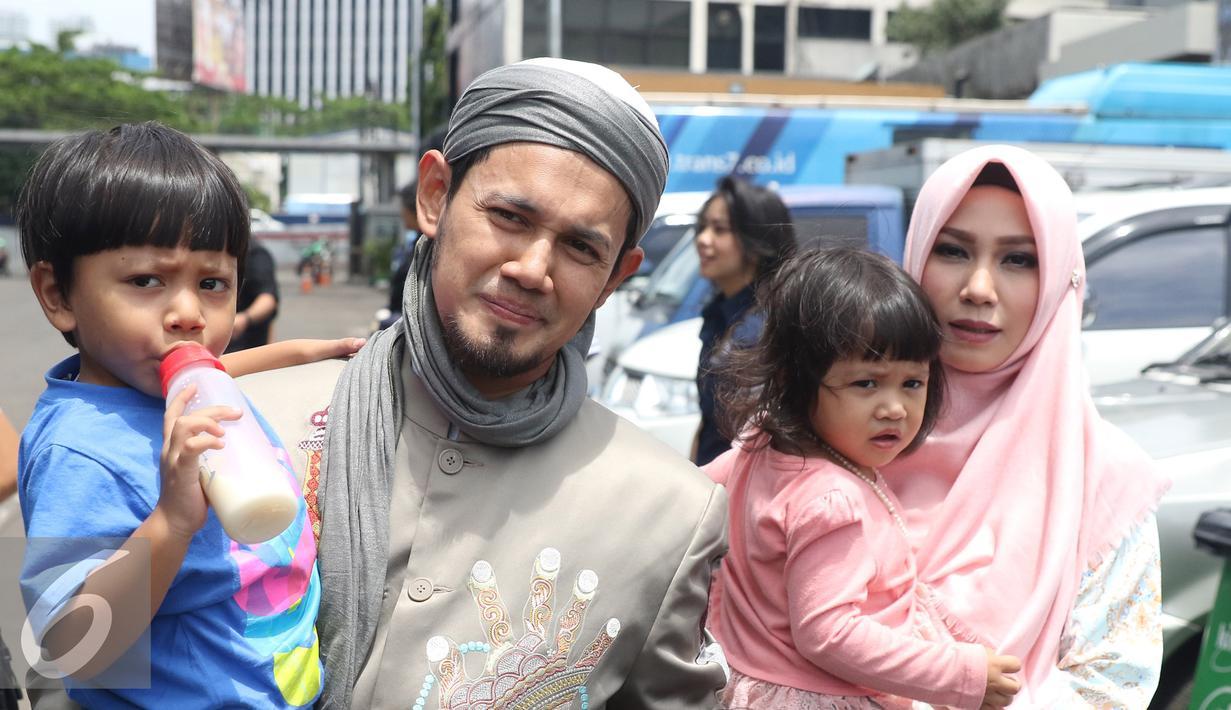 Ustadz Guntur Bumi (UGB), Puput Melati dan kedua anaknya usai mengisi sebuah acara di kawasan Tendean, Jakarta, Rabu (16/11). UGB dan Puput mengaku sudah kembali rujuk pasca cerai pada Januari 2014 silam. (Liputan6.com/Herman Zakharia)
