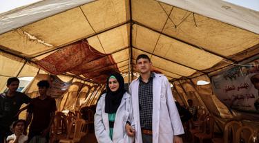 Pasangan petugas medis Muadh Al-Raqab (kanan) dan Hadeel Al-Najjar yang baru menikah berfoto di luar tenda di jalur Gaza selatan, Palestina (2/5). Petugas medis ini harus melangsungkan pernikahannya di dalam tenda. (AFP Photo/Said Khatib)