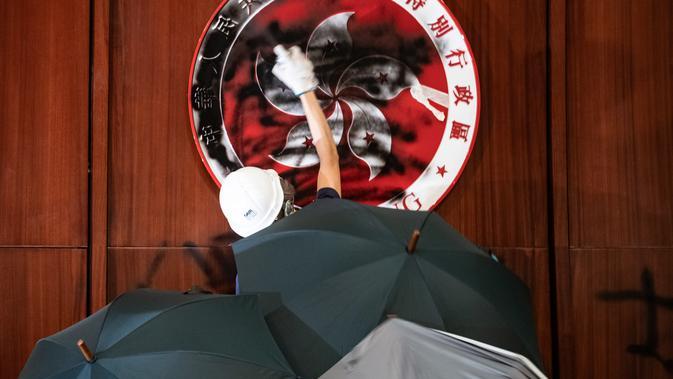 Demonstran merusak simbol Hong Kong di Gedung Parlemen dalam aksi demonstrasi, Senin (1/7/2019) malam waktu setempat. (AFP/Philip Fong)