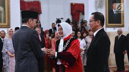 Presiden Joko Widodo bersalaman dengan hakim MK yang baru, Enny Nurbaningsih usai pelantikan, Jakarta, Senin (13/8). Jokowi mencari pengganti Maria melalui tim panitia seleksi hakim MK yang dipimpin mantan Hakim MK Harjono. (Liputan6.com/Biropers)