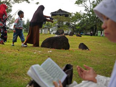 Anggota keluarga menabur bunga di salah satu makam korban tsunami Aceh di sebuah kuburan massal di Aceh, Senin (26/12). Warga Aceh memperingati 12 tahun gempa dahsyat berkekuatan 9,3 SR disusul tsunami pada Minggu 26 Desember 2004 (CHAIDEER MAHYUDDIN/AFP)