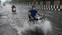 Pengendara motor melewati jalan yang tergenang air saat hujan lebat di New Delhi, India (1/9/2021). Stasiun cuaca mencatat curah hujan 112,1 mm dalam 24 jam yang berakhir pada hari Rabu pukul 08.30 waktu setempat. (AFP/Prakash Singh)
