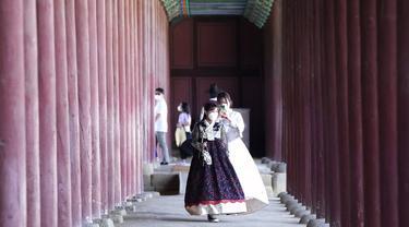 Seorang wanita mengenakan masker sebagai tindakan pencegahan terhadap virus corona mengambil foto temannya saat mereka mengunjungi Istana Gyeongbok untuk merayakan liburan Chuseok, Hari Thanksgiving versi Korea, di Seoul, Korea Selatan, Rabu (22/9/2021). ( AP Photo/Ahn Young-joon)
