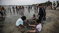 Pengunjung bermain di Pantai Karnaval Ancol, Jakarta, Jumat (14/5/2021). Pemprov DKI Jakarta pada libur Lebaran 2021 membuka sejumlah tempat wisata, salah satunya Ancol. (Liputan6.com/Johan Tallo)