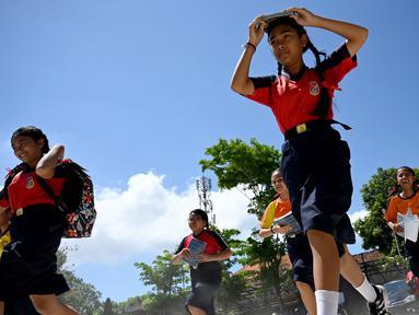 Sejumlah pelajar berlari saat mengambil bagian dalam latihan simulasi gempa bumi dan tsunami di Jimbaran, Bali (5/11/2019). Latihan dilakukan untuk memberikan pengajaran kepada siswa agar mengantisipasi bahaya bencana gempa bumi dan tsunami yang bisa datang sewaktu-waktu. (AFP Photo/Sonny Tumbelaka)