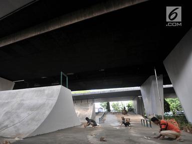 Aktivitas pekerja menyelesaikan pembangunan arena papan seluncur atau skate park dan lintasan sepeda BMX di kolong Flyover Slipi, Jakarta, Kamis (13/12). Pemprov DKI Jakarta melalui Suku Dinas Kehutanan membangun skate park. (Merdeka.com/Iqbal S. Nugroho)