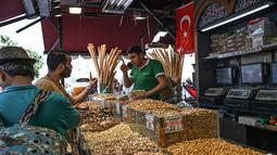 Pedagang melayani pembeli di Spice Bazaar yang bersejarah di distrik Eminonu di Istanbul, Turki (13/7/2019). Tempat tersebut menjadi spesial karena berbagai macam rempah-rempah pedas khas Turki dijual disitu. (AFP Photo/Ozam Kose)
