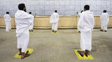 Jemaah haji melangsungkan lontar jumrah dengan menerapkan jaga jarak aman untuk menghindari penularan COVID-19 di Mina, Arab Saudi, Jumat (31/7/2020). Ritual melempar batu ke pilar ini menjadi simbol merajam setan. (Saudi Ministry of Media via AP)