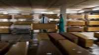 Pekerja memindahkan peti mati berisi korban meninggal akibat virus corona COVID-19 di kamar mayat Collserola, Barcelona, Spanyol, 2 April 2020. Menurut Universitas Johns Hopkins pada 6 April 2020 pukul 18.01 WIB, total kasus COVID-19 secara global sebanyak 1.286.409. (AP Phooto/Emilio Morenatti)