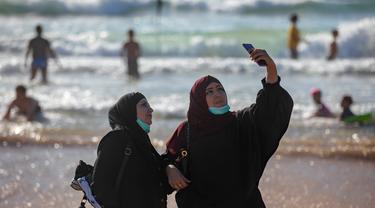 Wanita Palestina berselfie selama liburan Idul Fitri, di pantai laut Mediterania di Tel Aviv, Israel (25/5/2020).  Idul Fitri menandai akhir bulan suci Ramadhan, perayaan tiga hari yang biasanya menggembirakan telah berkurang secara signifikan karena pandemi coronavirus. (AP Photo/Oded Balilty)