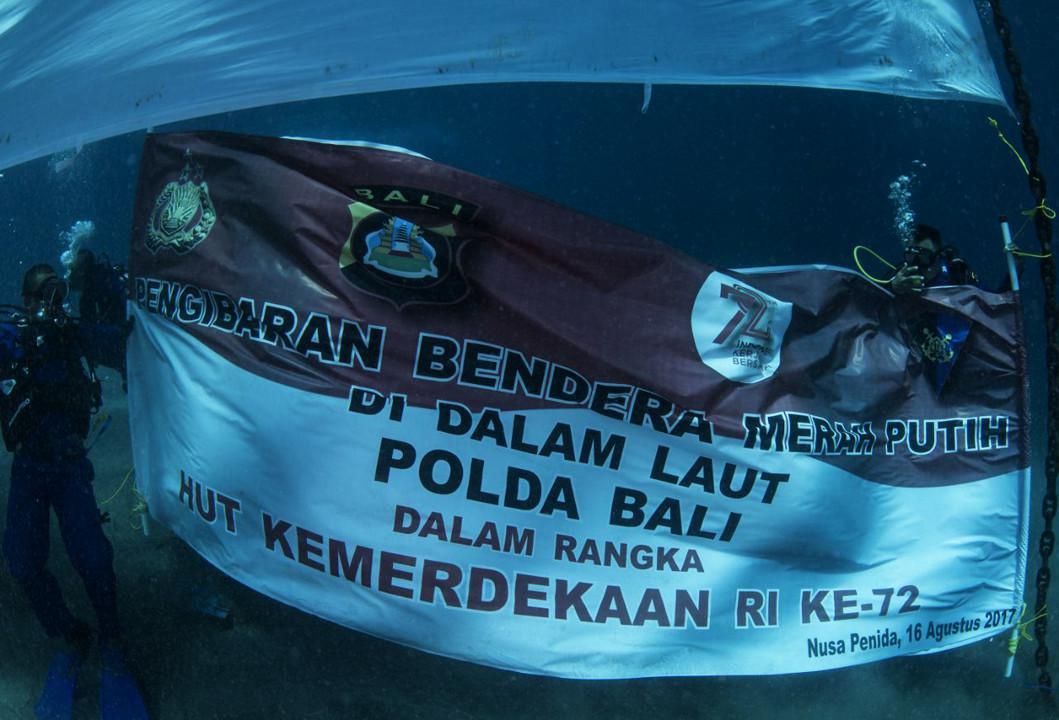 Dalam rangka memperingati HUT ke-72 RI, Polda Bali mengibarkan bendera merah putih ukuran 5x10 meter di bawah laut di perairan Crystal Bay, Nusa Penida, Bali. (Liputan6.com/Dewi Divianta)