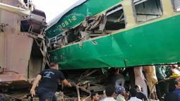 Tim penyelamat dan penduduk setempat berkumpul di dekat kecelakaan yang terjadi antara dua kereta di distrik Rahim Yar Khan, Pakistan, Kamis (11/7/2019). Insiden ini menyebabkan setidaknya sembilan orang tewas dan lebih dari 60 lainnya luka-luka. (Photo by STR / AFP)