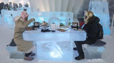 Foto yang diambil 13 Januari 2020 menunjukkan orang-orang menikmati hot pot di meja dan kursi berukir es di dalam igloo selama Festival Es dan Salju Internasional Harbin tahunan.  Restoran berbentuk rumah salju bangsa Eskimo ini hadir untuk memberikan sensasi makan malam yang berbeda. (STR/AFP)
