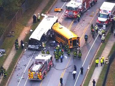 Petugas personel darurat dikerahkan ke lokasi kecelakaan sebuah bus komuter dan bus sekolah yang mengalami tabrakan di Baltimore, Maryland, Selasa (1/11). Sebanyak enam orang tewas dan sepuluh lainnya terluka akibat insiden itu. (WBAL-TV via AP)