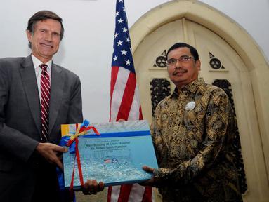 Duta Besar AS untuk Indonesia, Robert O'Blake Jr (kiri) menyerahkan dokumen penelitian dan dokumentasi eks rumah Raden Saleh di Jakarta, Selasa (26/4/2016). Bangunan ini satu dari dua karya arsitektur Raden Saleh. (Liputan6.com/Helmi Fithriansyah)