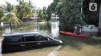 Warga beraktivitas menggunakan perahu melintasi mobil terendam banjir rob di Kompleks Perumahan Pantai Mutiara, Pluit, Jakarta, Minggu (7/6/2020). (merdeka.com/Iqbal S. Nugroho)