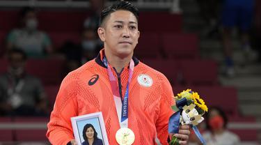 Riyo Kiyuna menjadi atlet pertama Jepang yang mampu merebut emas pada cabang olahraga Karate di Olimpiade Tokyo 2020. Gelar Olimpiadenya dedikasikan kepada mendiang ibunya yang terwakilkan dari sebingkai foto yang ia bawa ketika penyerahan medali. (Foto: AP/Vincent Thian)