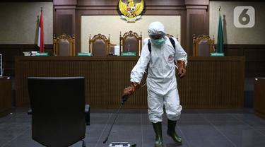 Petugas Palang Merah Indonesia saat melakukan penyemprotan cairan disinfektan di salah satu ruang sidang Pengadilan Negeri Jakarta Pusat, Rabu (18/3/2020). Penyemprotan cairan disinfektan untuk mencegah penyebaran virus corona COVID-19. (Liputan6.com/Helmi Fithriansyah)