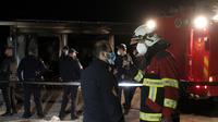 Petugas pemadam kebakaran berbicara satu sama lain berdiri di dekat rumah sakit darurat yang terbakar di kota Tetovo, Makedonia Utara, Kamis (9/9/2021). Kebakaran terjadi Rabu malam di rumah sakit darurat untuk pasien COVID-19. (AP Photo/Boris Grdanoski)